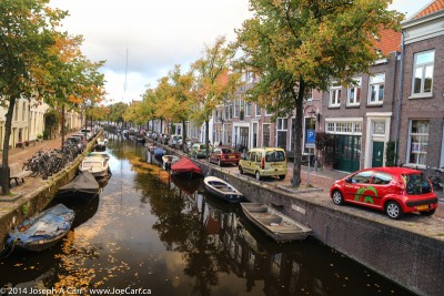 Fall colours along a canal with car, boat and bicycle parking in Haarlem