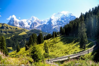 Eiger, Monch and Jungfrau peaks, alpine meadow and the railway