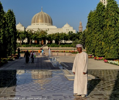 Our guide Yaqoob poses in front of the Sultan Qaboos Grand Mosque gardens