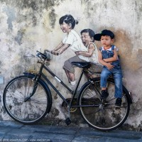 A boy sitting on street art along Lebuh Armenian street in Georgetown, Penang, Malaysia