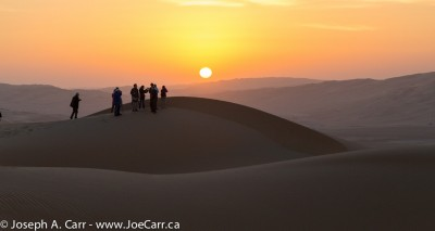 Group on the sand dunes at sunrise near Liwa Oasis