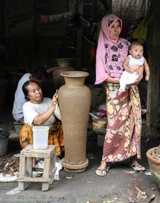 Woman making a tall pot with a younger woman holding a baby, Banyu Mulek, Lombok, Indonesia