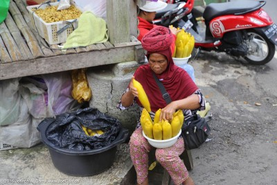 Woman selling corn beside a local fruit, vegetable and clothing market in Bali, Indonesia