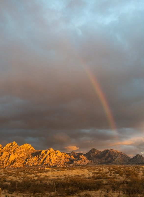Sunset lighting the Dragoon Mountains with a rainbow in front of the storm clouds